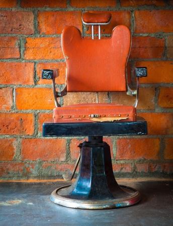 peluquero: La vieja silla de barbero vendimia sobre la pared de ladrillo