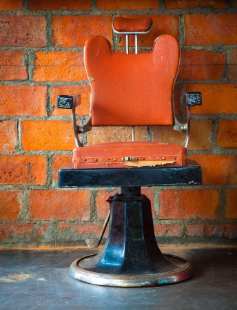 barber chair: The old vintage barber chair over brick wall