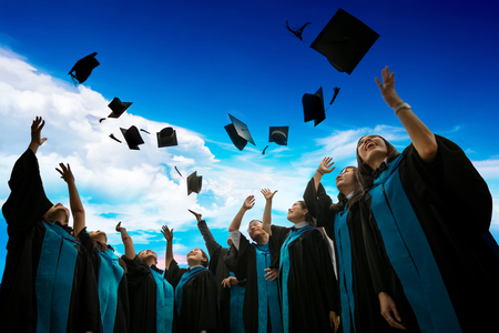 Group of graduates with congratulations throwing graduation hats in the air celebrating. Successful education concept.