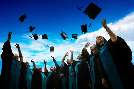 Group of graduates with congratulations throwing graduation hats in the air celebrating. Stock Photo