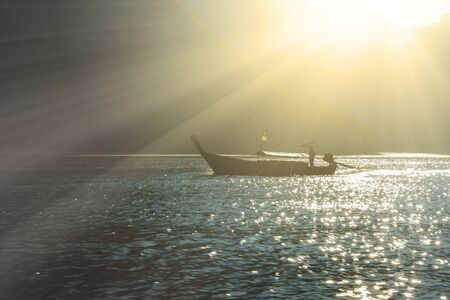 Lens flare image of fishing boat sailing in the sea at Krabi province, Thailand.