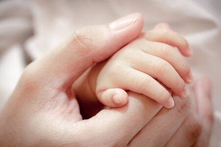 Close up and selective focus at fingers of baby newborn with hand of his mother.