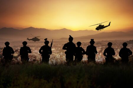 Silhouette of 8 armies standing and ready to attack the town below in the evening. Conceptual of war.