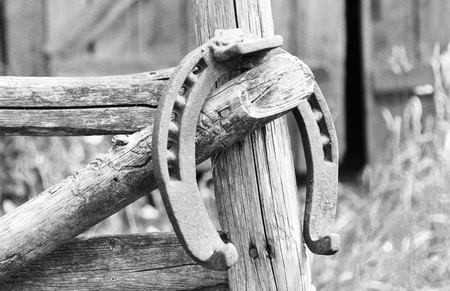 Antique rusty horseshoe fixed on nails on old wooden surface Stock Photo
