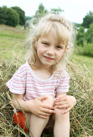 Girl and hay. A little girl is shoveling hay. Help with the housework. Summer in the countryside. Vacation for children. A stack of hay