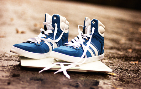 Mens blue sneakers on a white square scales on the asphalt road, autumn. close-up