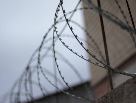 a wall, a fence behind it is the prisoners who are convicted. Barbed wire Stock Photo
