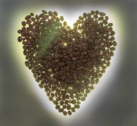 heart from coffee beans. Illuminated from below, or without illumination, a wooden background.