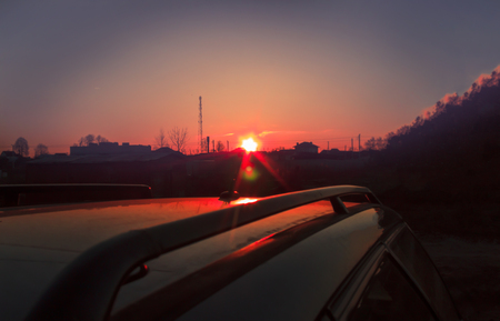 Summer. Late evening. The sun almost sat down. The car is dark. Stock Photo