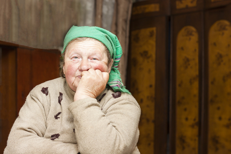 An old woman is sitting on a chair. Clothes are old and dirty. Shallow depth of cut. Imagens