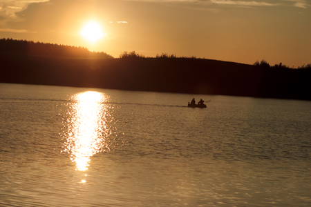 Summer evening near the lake. The sun was almost gone. Fishermen are fishing on the lake