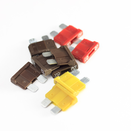 car fuse. red, yellow, dark. close-up on a white background Stockfoto