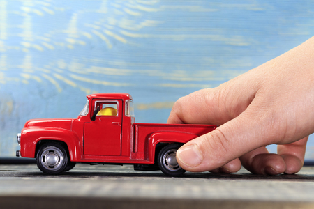 red pickup on dark wooden background withstand the human hand. Stock Photo