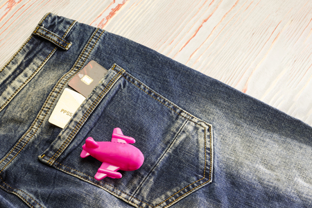 Blue jeans back pocket view - bank plastic card and passport. next to the pocket is a children's toy airplane