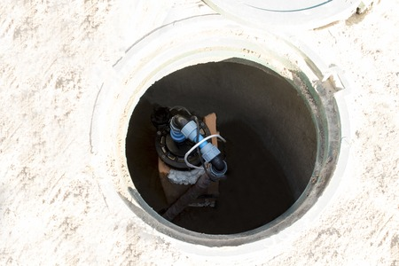 sun, hot and white sand. open access hatch, inside the well that pumps water. Stock Photo