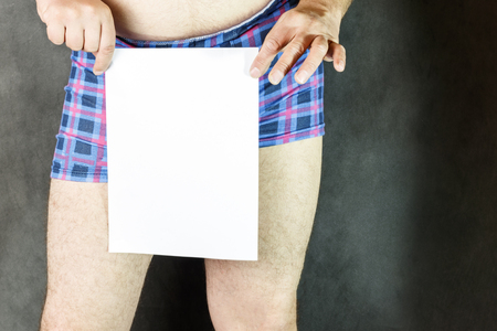 Young man in shorts, a sheet of white paper. close-up on shorts. and shows the field up.