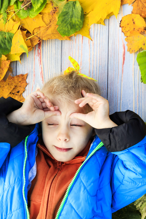 very yellow. funny girl lying on a fallen leaf. blue jacket. eye squeezed. close-up.