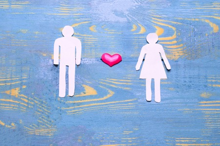 he, she, and children cut out of paper the relationship of family to each other. love and hormone should be in the family. photo on a blue background Stock Photo