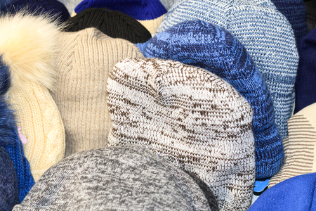 winter hats for sale, hanging on the wall, childrens adults. Standard-Bild