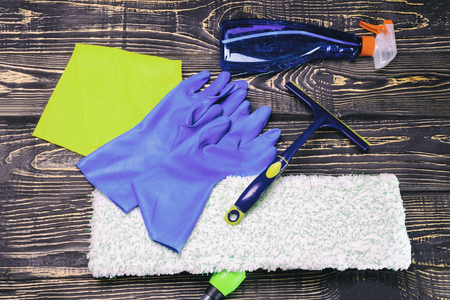 dark wooden background, mop and gloves. there is a scraper for glasses and cleaning products. there is tanirovanie Stock Photo