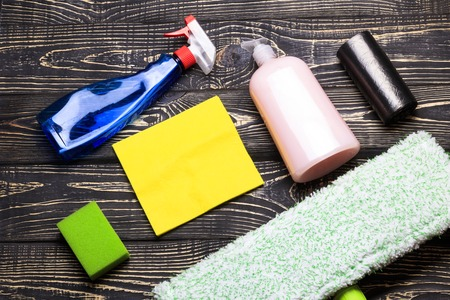 dark wooden background, mop and gloves. there is a scraper for glasses and cleaning products. there is tanirovanie. Stock Photo