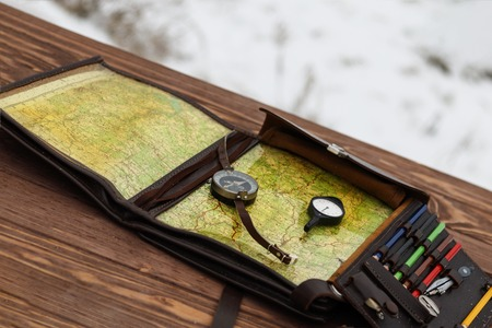 Winter is snowing. wooden table. There is a compass and odometer. there is toning.