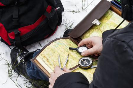 it is cold in winter, it is snowing. Girl with a compass map and odometer in hand, paves the route. there is toning.