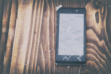 broken mobile phone on a wooden background. Mobile phone repair. there is toning