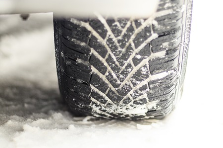 Winter is snowing. car wheel winter tires. close-up. have toning. 免版税图像