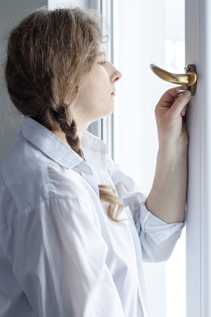 Young woman 30 years old. unscrew the screw with a screwdriver. Im going to fix the pen on the glass Stock Photo