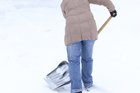 Winter is a lot of snow. A young girl, cleans, proud of doing the big shovel work. Stock Photo