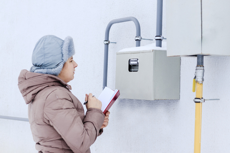 winter, snow, cold. the girl, the engineer, the worker records the readings of the sensors and pressure gauges. They are located on the street and located in a special box. Banco de Imagens - 116471871