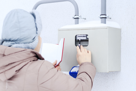 winter, snow, cold. the girl, the engineer, the worker records the readings of the sensors and pressure gauges. They are located on the street and located in a special box.