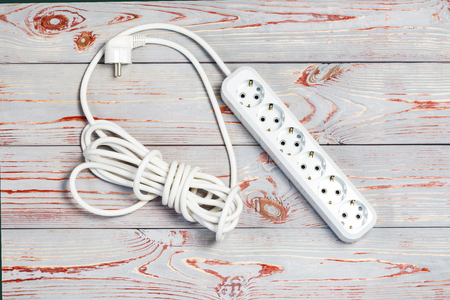 wooden background in retro style, on it is an extension cord with European cuts