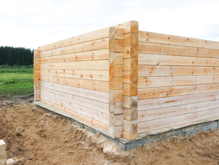 the beginning of the construction of a wooden house. The bar is profiled and falls into the groove. Laying in the corner. half laid and next still material Stock Photo