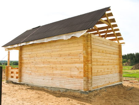 the beginning of the construction of a wooden house. The bar is profiled and falls into the groove. Laying in the corner. half laid and next still material. Stock Photo