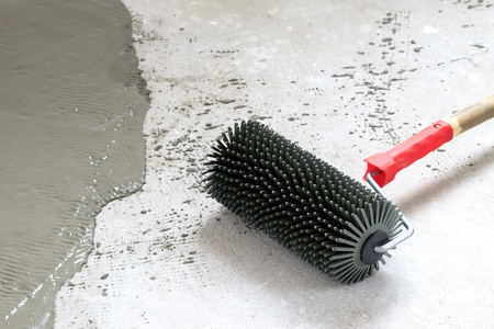 concrete floor. on the horizon. close-up. needle roller for removing air bubbles. have toning. then there will be painting. 免版税图像