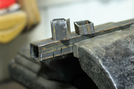 metal clutches in them clamped square tube. there is still a piece on top. shallow depth of cut Reklamní fotografie