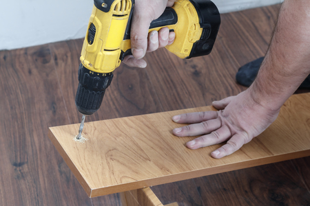 is the process of assembling furniture from chipboard. in the hands of a rechargeable screwdriver for tightening screws