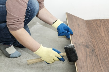 master in blue gloves makes laying. floorboard. there is a level. and rubber hammer