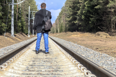 Railway. A man in a dark coat stands to us. on this backpack. there is toning