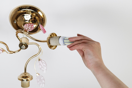 female hand inserts a light bulb into the threaded socket. Installation of household LED lamps of corn type, in the lamp holder, there is a toning.