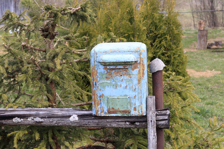 mailbox. it's made of metal. the paint on it almost peeled off. standing on the street.