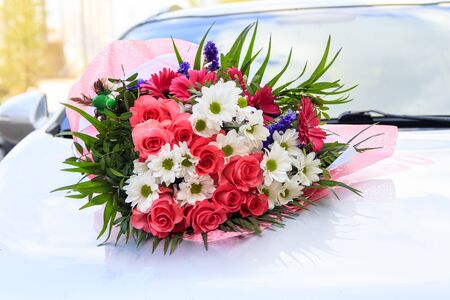 A bouquet of flowers is located on the car. natural lighting. flowers of roses and daisies