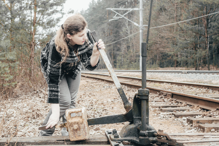 The girl manually passes the arrows on the railroad tracks. daylight. there is toning