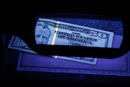 Fifty dollars in the photo. US banknotes. Equipment for in-depth inspection of money. Checking bills in ultraviolet light. Fake money or financial crisis concept