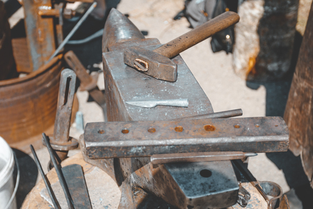 anvil. on it lies a hammer. blacksmith works. close-up