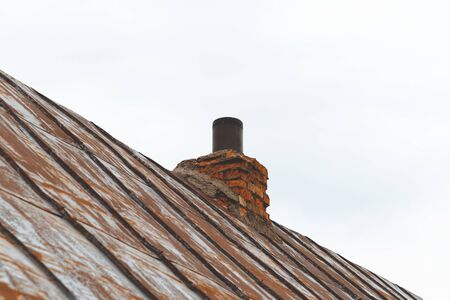 metal roof, the paint almost disappeared. on her chimney. trumpet and kerpich Imagens