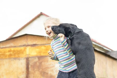 daylight. little girl playing with a black dog on the lawn in the yard