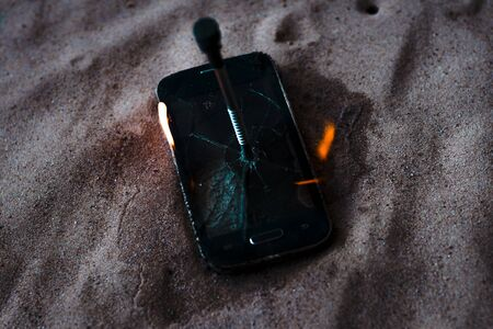 cellular telephone. on the beach sand. it has a metal nail in it. it burns with open fire.